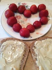Dinkelbrot mit Mandelmus und Honig, dazu Erdbeeren
